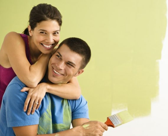 happy couple saving money by painting home during new home construction